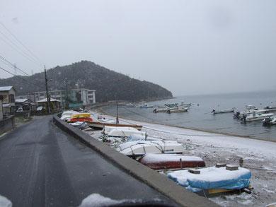 2010年3月に珍しく雪が降った時の写真です。山の下に小さく見える3階建てが中学校です。