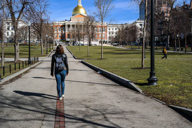 me a girl walking towards the massachusetts state hall on the freedom trail in boston in the park next to park street
