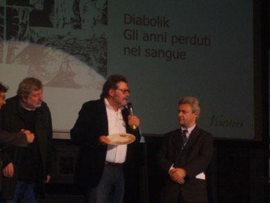 Mario Gomboli ha appena ricevuto il premio dalle mani del cantautore Francesco Guccini