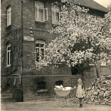 """Auf diesem Foto aus den 30ern ist noch das Schild mit der Aufschrift """"Cigarren & Cigaretten Geschäft Heinrich Sandvoss"""" zu erkennen. Im Vordergrund: Heinrichs Töchter."""