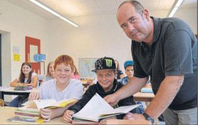 Schauen sich gemeinsam die neuen Schulbücher an: (von links) Marco Staube, Thorben Weber und Lehrer Ralf Martin am ersten Tag in ihrer Klasse 5b an der Cornelia-Funke-Schule. Foto: Pflug