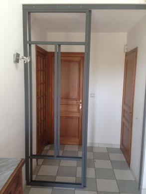 Une verrière de fabrication artisanale soignée avec une porte coulissante.