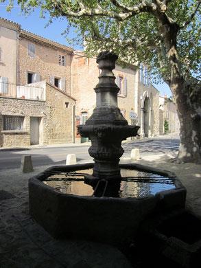 Vue d'ensemble de l'entrée du village avec sa fontaine