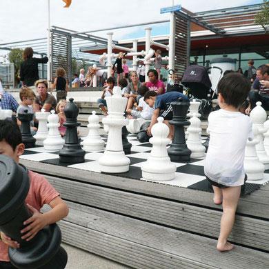 屋上広場でビショビショになりながら巨大なチェスで遊ぶ子供たち。