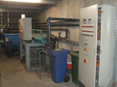 Alte Kältemaschine mit 2 offenen Systemen Kaltwasser- und Kühlwasser Behälter im Hintergrund und Schaltschrank rechts