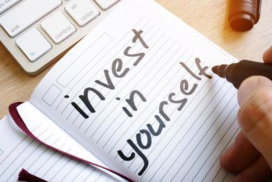 Notizheft mit Text invest in yourself in schwarzer Schrift liegt auf dem Schreibtisch eine Tastatur ist zu sehen