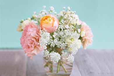 ガラスの瓶に活けられたピンクのバラ、ピンクのカーネーション、カスミソウ。