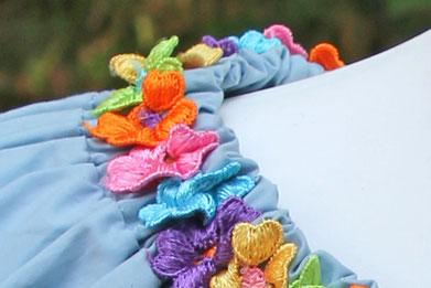 Gestickte Blüten in Regenbogenfarben auf hellblauer Tunika
