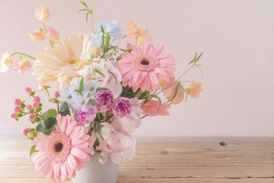 ピンクのノートパソコン。傍らにペン立てと観葉植物。積まれたノート、ゼムクリップ、付箋、はさみ。