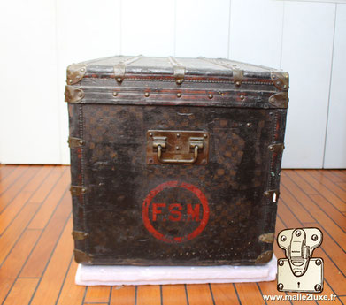 Louis Vuitton initials on an old checkered trunk