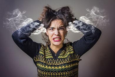 Wütende Frau, die sich die Haare rauft.