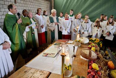 Geistliche und Messdiener am Erntedank-Altar in der Scheune
