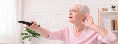 Frau hält linke Hand hinter das Ohr und in der rechten die Fernbedienung