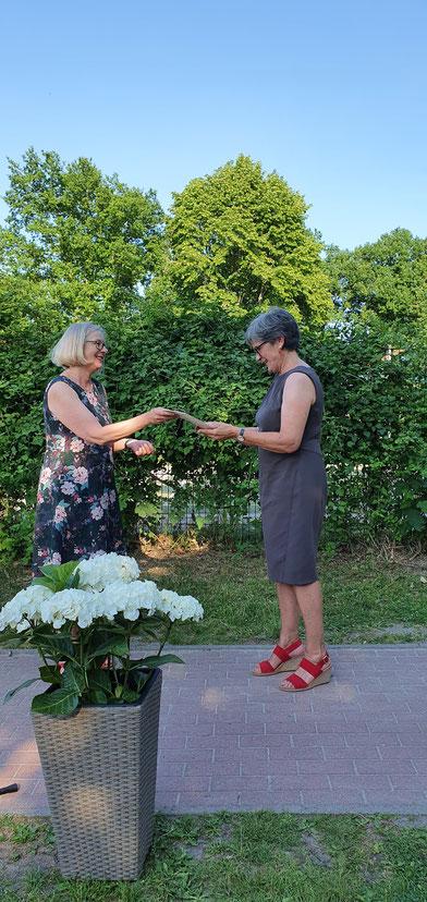 Schulrätin Katrin Thomas überreicht Rektorin Margrit Biesenack die Urkunde über den Eintritt in den Ruhestand.