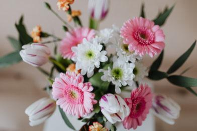 レース編みのテーブルクロスのうえに広げられたノートとボールペン。紅茶の入った白のカップ&ソーサ。薄いピンクのバラのアレンジメント。
