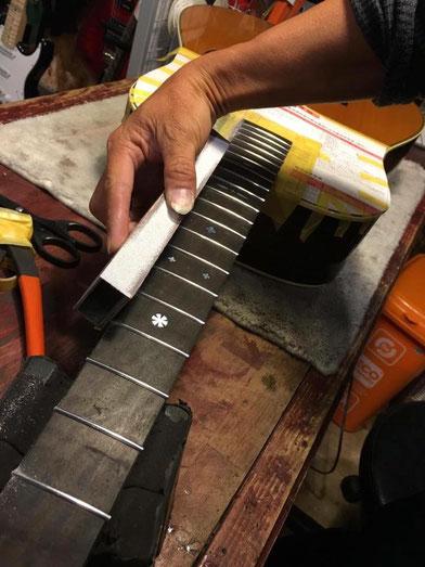ギターのネックに沿ってステンレスフレットをやすりがけしている作業