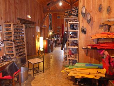 Cette image représente une vue de l'atelier des sabots d'isa, là ou l'on fabrique à la main et sur mesure des sabots qui se prennent pour des chaussures. Tout est en bois, paisible, il y a des semelles et des cuirs en couleur partout.