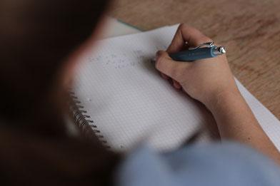 Schülerin schreibt in Block