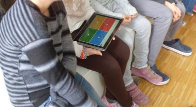 Schüler/-innen mit einem Tablet
