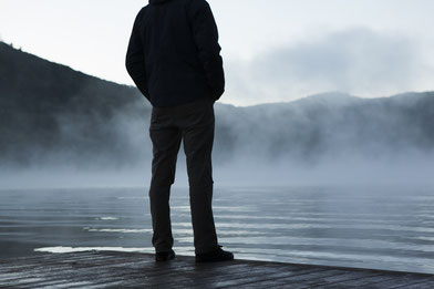 Man is thinking by a lake