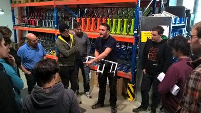 Werkstattleiter Arne Ulrich (Mitte) erläutert eine Vorrichtung zum Aufbringen von Dekoraufklebern bei Trike-Rahmen. / Foto: HP Velotechnik
