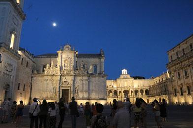 Abenstimmung an der Piazza del Duomo in Lecce, am dunkelblauem Himmel leuchtet der Mond, im Vordergrund sieht man viele Menschenn