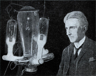Nikola Tesla is shown in his laboratory with late type mercury arc rectifier tubes. When operating, these tubes give off a violet glow.