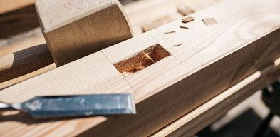Ein Holzbalken mit Stemmeisen und Holzhammer
