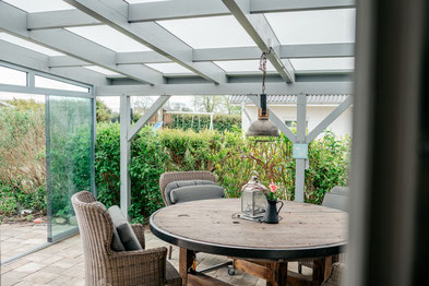 Tisch und Stühle auf einer Terasse mit Vordach aus Holz