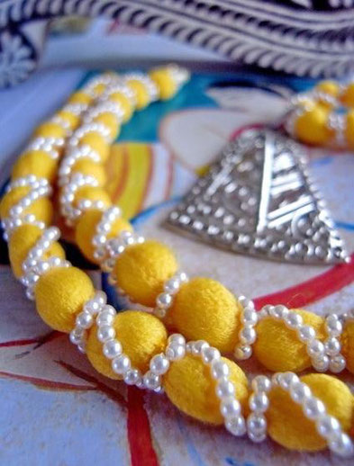 Pinjara necklace with silver pendant; close-up of canary-yellow, cottonsilk-and-ivory-pearl chain