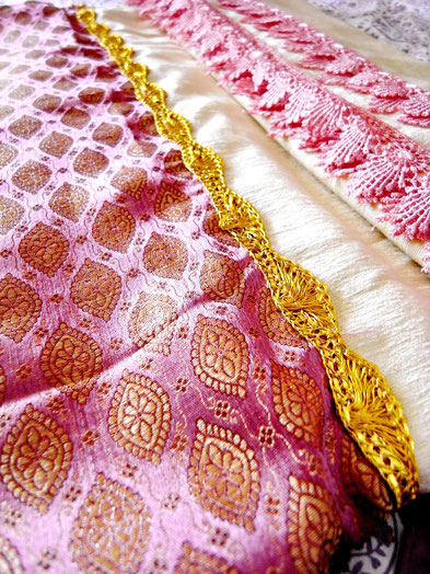 Close up of pewter pattern, gold ribbon and pink lace on joined, cream velveteen & grape-coloured silk brocade Indian throw
