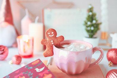 広げられた白紙のノート。オレンジピンクのデイジーとバラの花束。
