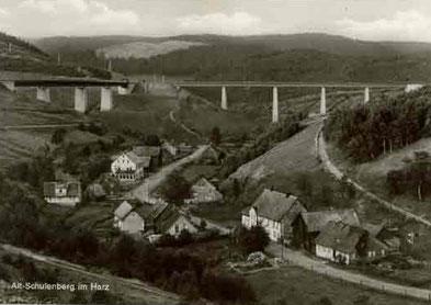 Schwarzweißfoto eines Dorfs in einem Tal, über das zwei große Brücken führen