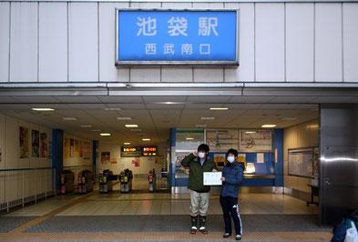 東京・池袋駅で集合。電車で秩父まで向かいます。「雪かきボランティア」という紙を掲げて、参加者を待つ山田君(右)たち。