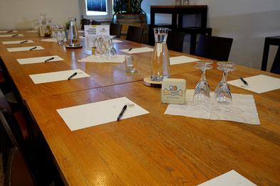 Tisch mit Schreibblöcken, Stiften, Gläsern und Getränken