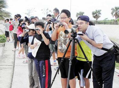 双眼鏡で野鳥を観察する参加者=真栄里海岸