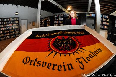 Der Reichsbanner sieht nun wieder aus wie neu. Angelika Arenz-Morch, stellvertretende Leiterin des NS-Dokumentationszentrums in der Gedenkstätte KZ Osthofen, hält und begutachtet den Reichsbanner.