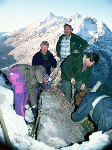 Manganbergwerk Starlera 15. Dezember 1994. Der 1500 kg schwere Eisen-Mangan-Erzblock wird zum Abtransport mit dem Hubschrauber vorbereitet. Bergbau in Innerferrera, Schams.