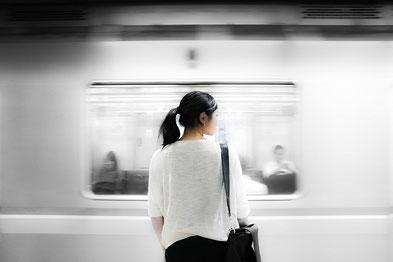 アネモネ法律事務所への電車を待つ女性