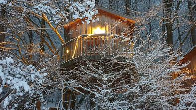Baumhaus im Schnee mit Lichterkette.