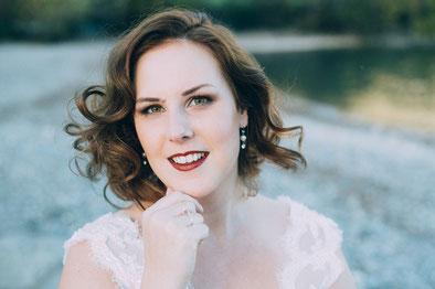Schöne Braut mit Locken und roten Lippen