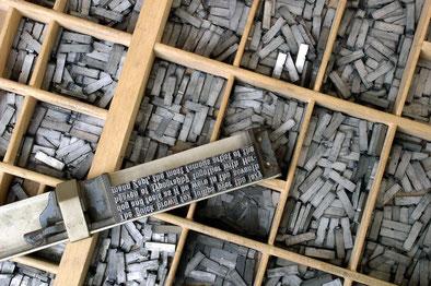 Setzkasten und Winkelhaken mit gesetzten Schriftzeilen
