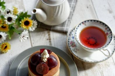カッティングボードに盛りつけられた抹茶ケーキ。ミントの葉とラベンダーの花。
