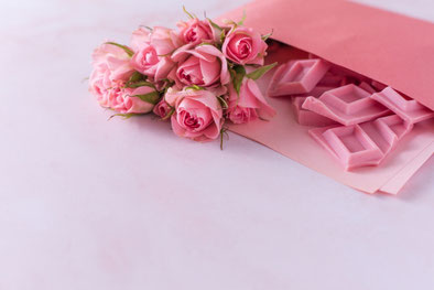 ピンクの小さなバラのコサージュ。ピンクの封筒からこぼれ出たイチゴチョコ。