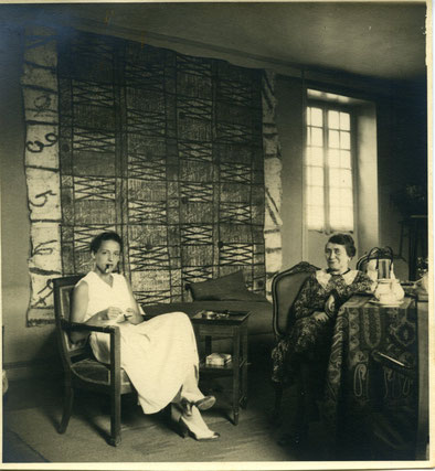 Eve Curie et Marie-Thérèse Chadourne assise dans le salon en fumant à Cublac, Le Bousquet