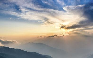 Ein leicht wolkiger Himmel verdeckt gerade so die Sonne, die totzdem mit ihren Strahlen das Bild durchdringt. Es steht hier für das Element Luft in der hawaiianischen Massage und Körperarbeit Lomi Lomi.