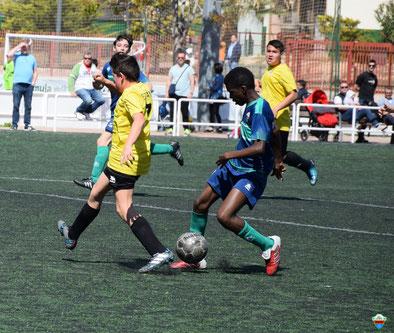 Imagen de un jugador de raza negra controlando el balón en el campo de fútbol e intentando llevarse la pelota del jugador del equipo contrario que va vestido de amarillo y negro.