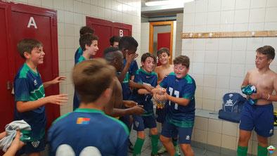 Muchos niños celebrando la vitoria en el vestuario derramando champín