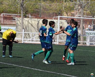 Cuatro niños celebran un gol en el campo de fútbol