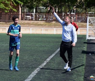 Un entrenador vestido con chaqueta deportiva blanca y pantalones largos negro levanta la mano llamando a un jugador en el terreno de juego